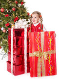 Child  holding gift box by christmas tree. Stock Photo