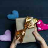 Child holding a gift box with golden ribbon Stock Images
