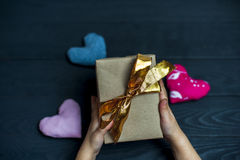 Child holding a gift box with golden ribbon Royalty Free Stock Image