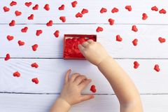Child holding gift box and hearts for Mother`s Day on white wood background. Wedding and Valentine concept. Happy Valentine`s Day stock images