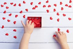 Child holding gift box and hearts for Mother`s Day on white wood background. Wedding and Valentine concept. Happy Valentine`s Day stock photography