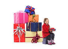 A child holding a gift next to a pile of gifts Stock Photo