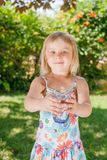 Child holding glass of drinking water outdoors royalty free stock photo