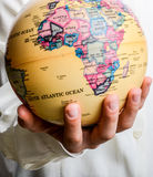 Child holding a globe in hand. Child holding a small model globe in hand on white background Stock Photos