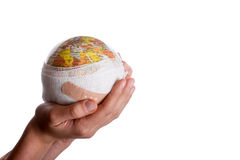 Child holding a globe with plaster. In his hand on a white background Stock Photography