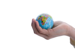 Child holding a globe. Child holding a small globe in hand on white background Stock Image