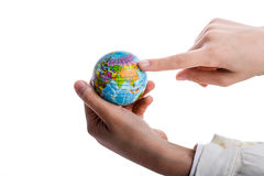 Child holding a globe. Child holding a small globe in hand on white background Royalty Free Stock Images