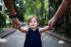 Child holding grandparents hands in a park. Happy childhood stock images