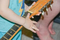 Child holding a guitar royalty free stock photos