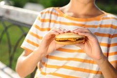 Child holding hamburger closeup. Boy holding tasty hamburger at striped background Royalty Free Stock Image