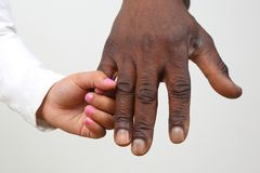 Child holding the hand of a dark-skinned father