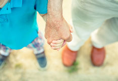 Child holding hand of senior man in the nature Royalty Free Stock Photography