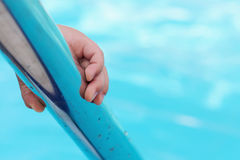 Child holding a handrail in swimming pool. Child`s hand holding a handrail in swimming pool stock photography