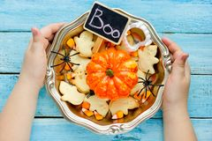 Child holding in hands traditional halloween treats in bowl. Top view stock images