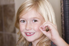 Child holding her front tooth Stock Image