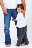 Child holding his father leg - safety and security concept stock photography