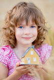 Child holding house in hands Stock Image