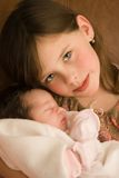 Child holding infant. Young girl child holding new infant family member royalty free stock image
