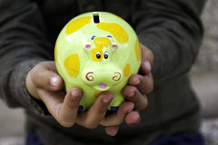 Child holding a money box. Child with a money box in the hands Stock Image