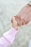 Child holding mother's hand Stock Images