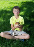 Child holding a  mushroom cep  in hand on a background of green Stock Images