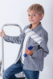 Child holding paint roller. Standing on ladder Stock Images