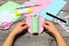 Child holding paper butterfly crafts in hands. Child shows a fun paper crafts. Stationery on an old wooden table. Children workplace. Summer children art craft Royalty Free Stock Photography