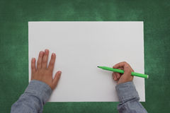 Child holding pen on blank sheet of paper Royalty Free Stock Image