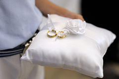 Child holding a pillow with the wedding rings Stock Photo
