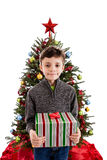 Child holding present in front of Christmas tree Royalty Free Stock Image