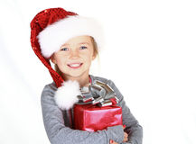 Child holding present wearing santa hat Stock Images