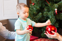 Child holding a red Christmas decoration. Royalty Free Stock Photo