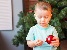 Child holding a red Christmas decoration. Royalty Free Stock Photography