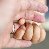 Child is holding a ringfinger of his father Stock Image