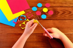 Child is holding scissors and paper and cut circle. Colorful paper sheets. Brown wooden background Royalty Free Stock Photo