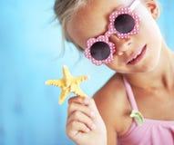 Child holding seashell Stock Images