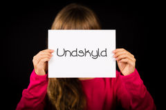 Child holding sign with Danish word Undskyld - Sorry. Studio shot of child holding a sign with Danish word Undskyld - Sorry Stock Image