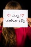 Child holding sign with Danish words Jeg Elsker Dig - I Love You Stock Photography