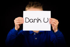 Child holding sign with Dutch words Dank U - Thank You. Studio shot of child holding a sign with Dutch words Dank U - Thank You royalty free stock photos