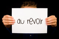 Child holding sign with French word Au Revoir - Goodbye Royalty Free Stock Image