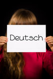 Child holding sign with German word Deutsch - German in English. Studio shot of child holding a sign with German word Deutsch - German in English Royalty Free Stock Image