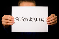Child holding sign with German word Entschuldigung - Sorry Stock Photography