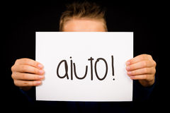 Child holding sign with Italian word Aiuto - Help Stock Images