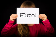 Child holding sign with Italian word Aiuto - Help Royalty Free Stock Images