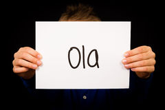 Child holding sign with Portuguese word Ola - Hello Stock Photo