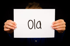 Child holding sign with Portuguese word Ola - Hello Royalty Free Stock Photos