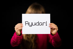 Child holding sign with Spanish word Ayudar - Help Royalty Free Stock Images