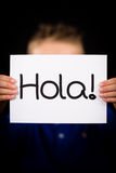 Child holding sign with Spanish word Hola - Hello Stock Photos