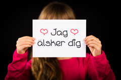 Child holding sign with Swedish words Jag Alsker Dig - I Love Yo Royalty Free Stock Image