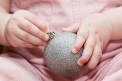 Child holding silver christmas ball Royalty Free Stock Photos